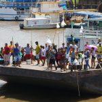 Händler mit Waren an Stangen warten auf die Ankunft des Schiffes