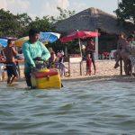 Verkäufer mit Karren im Wasser