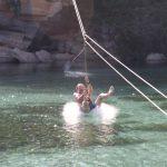 Jan an der Tirolesa hängend kurz vor dem Eintauchen ins Wasser