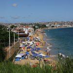 Schmaler Strand mit Sonnenschirmen und vielen Menschen