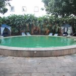 Hotel pool im Innenhof umgeben mit großen Bäumen